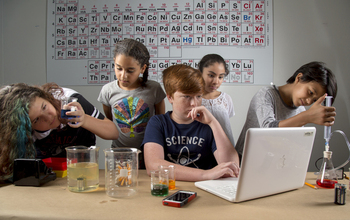 Students in front of a periodic table of elements using scientific equipment and technology.